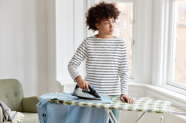 Przemyślana czarna młoda kobieta żelaznej koszuli męża z elektrycznym żelazkiem wygląda w zamyśleniu na bok