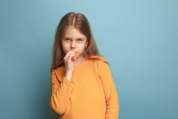 Przemyślana dziewczyna. smutna dziewczyna na niebieskim tle studio. wyraz twarzy i koncepcja emocji ludzi.