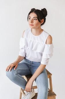 Przemyślana dziewczyna z fryzurą double buns patrząc na bok z rozmyślań spojrzeniem, siedząc w fotelu, na białym tle
