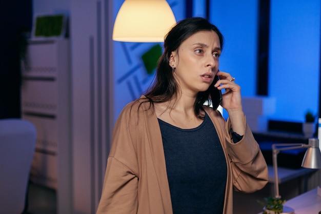 Przemyślana kobieta rozmawia na smartfonie z klientem o terminie. kobieta przedsiębiorca pracuje do późna w nocy w firmie robi nadgodziny w trakcie rozmowy telefonicznej.