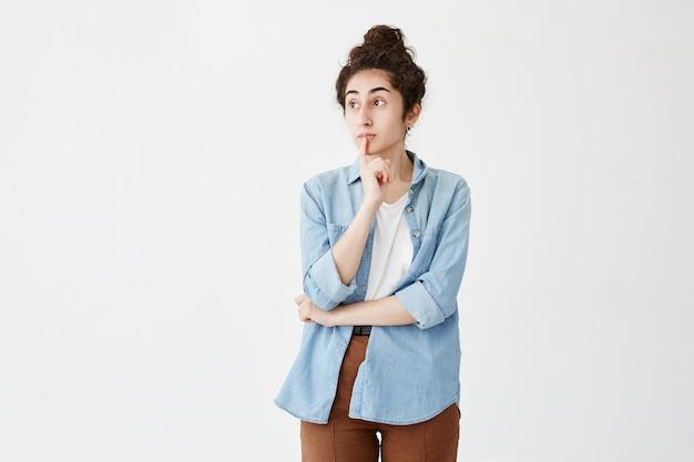 Przemyślana kobieta z kokardą do włosów, trzyma palec na ustach, z zamyślonym wyrazem twarzy, w dżinsowej koszuli i brązowych spodniach. młoda kobieta patrzy na bok, podejmując ważną decyzję