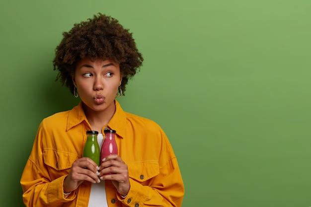Przemyślana ładna afroamerykańska kobieta trzyma szklane butelki świeżego koktajlu jabłkowego i truskawkowego, prowadzi zdrowy tryb życia, pije odżywczy napój organiczny, aby zachować kondycję, odizolowany na zielonej ścianie