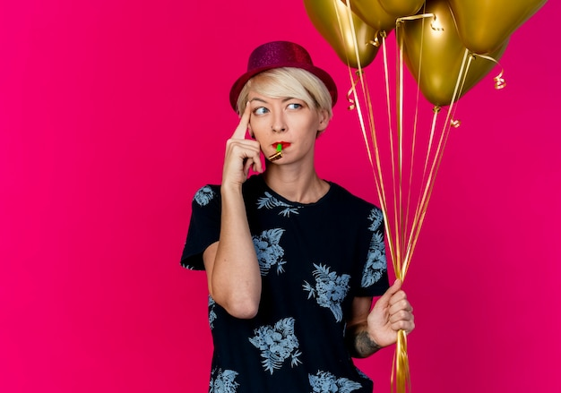 Przemyślana młoda blond impreza w kapeluszu imprezowym trzymająca balony i dmuchawę w ustach dotykająca świątyni palcem patrząc w bok na białym tle na szkarłatnym tle z przestrzenią do kopiowania