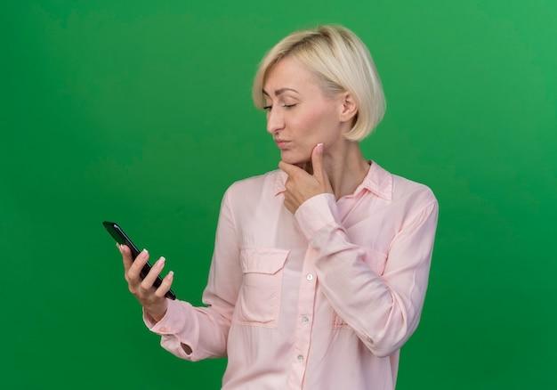 Przemyślana młoda blond słowiańska kobieta, trzymając i patrząc na telefon komórkowy i dotykając brody na białym tle na zielonym tle