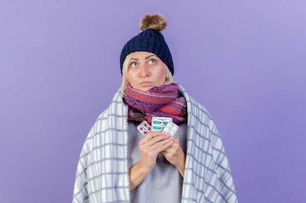 Przemyślana młoda blondynka chora słowiańska kobieta w czapce zimowej i szaliku owinięta w kratę trzyma paczki pigułek medycznych, patrząc w górę na fioletowej ścianie z miejscem na kopię