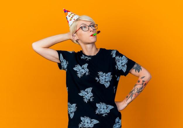 Przemyślana młoda blondynka imprezowa w okularach i czapce urodzinowej, patrząc z boku, trzymając rękę za głową i na talii, trzymając dmuchawę w ustach na białym tle na pomarańczowym tle