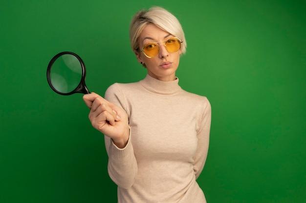 Przemyślana młoda blondynka w okularach przeciwsłonecznych, trzymająca szkło powiększające, trzymając rękę za plecami