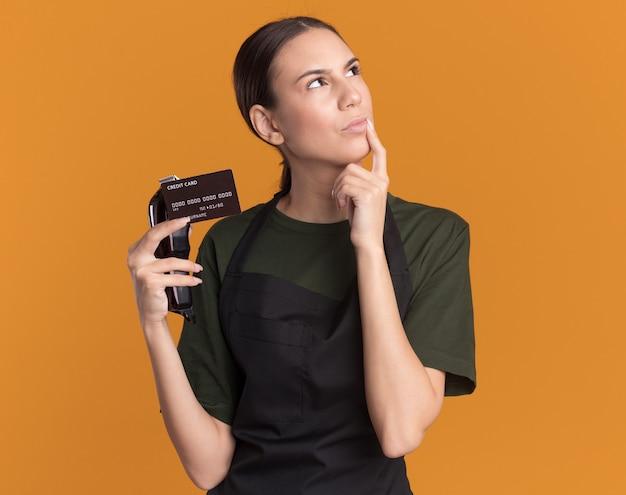 Przemyślana młoda brunetka fryzjerka w mundurze kładzie palec na brodzie, trzyma maszynki do strzyżenia włosów i kartę kredytową, patrząc w górę na pomarańczowej ścianie z miejscem na kopię