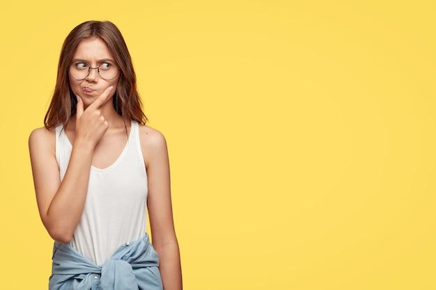 Przemyślana młoda brunetka w okularach pozuje na żółtej ścianie