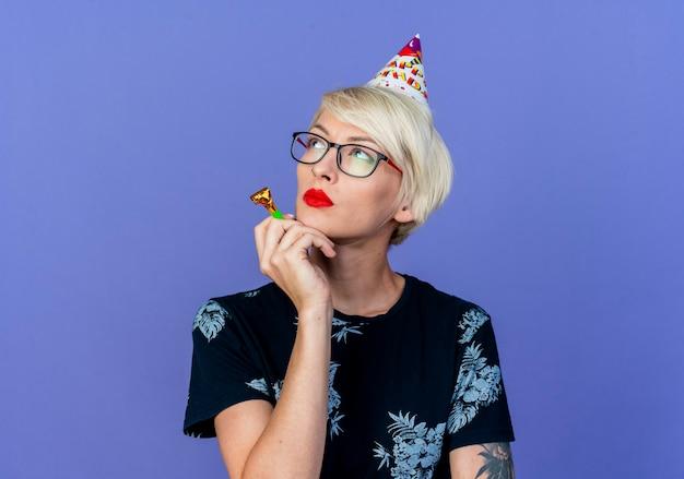 Przemyślana młoda dziewczyna blondynka w okularach i czapkę urodziny trzymając dmuchawę strony patrząc na bok na białym tle na fioletowym tle z miejsca na kopię