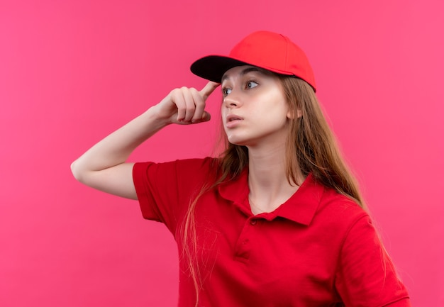 Przemyślana młoda dziewczyna dostawy w czerwonym mundurze kładąc palec na głowie patrząc na lewą stronę na na białym tle różowej ścianie