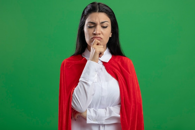 Przemyślana młoda dziewczyna superbohatera kaukaski trzymając rękę na łokciu i na brodzie, patrząc w dół na białym tle na zielonej ścianie z miejsca na kopię