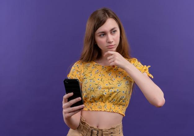 Przemyślana młoda dziewczyna trzyma telefon komórkowy i kładzie rękę na brodzie na odosobnionej fioletowej ścianie z miejsca na kopię