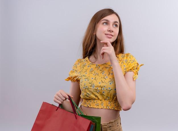 Przemyślana młoda dziewczyna trzymając papierowe torby i kładąc rękę na brodzie na na białym tle białej ścianie