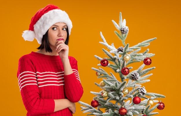 Przemyślana młoda dziewczyna ubrana w santa hat stoi obok ozdobionej choinki trzymając rękę na brodzie patrząc z boku na białym tle na pomarańczowej ścianie
