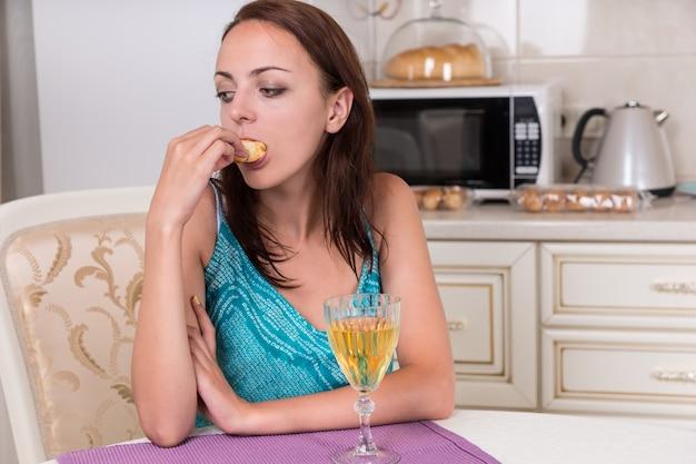 Przemyślana młoda kobieta jedzenie ciasteczek przy lampce wina w kuchni.