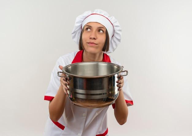Przemyślana młoda kobieta kucharz w mundurze szefa kuchni, trzymając garnek i patrząc w górę na białym tle na białej ścianie