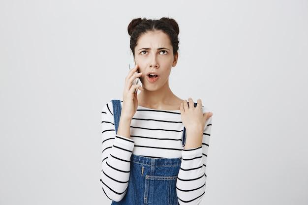 Przemyślana młoda kobieta ma rozmowę telefoniczną