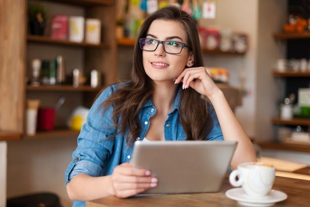 Przemyślana młoda kobieta za pomocą cyfrowego tabletu w kawiarni