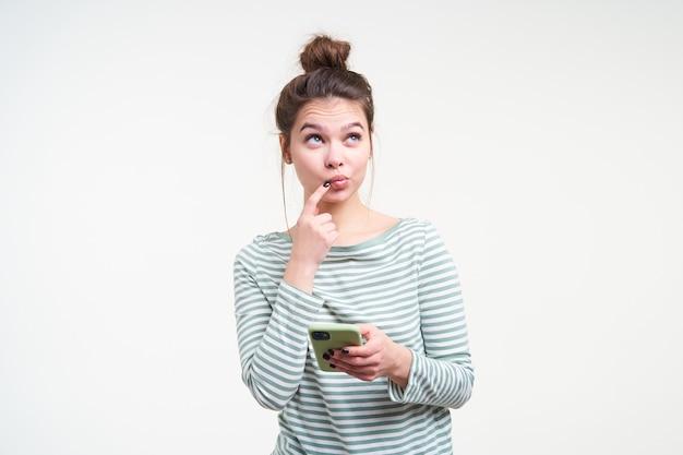 Przemyślana młoda ładna brązowowłosa kobieta z fryzurą w kok, trzymając palec wskazujący na wardze, patrząc w zadumie w górę, pozując nad białą ścianą