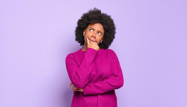 Przemyślana młoda ładna czarna kobieta patrząc w górę