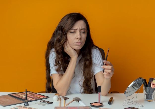 Przemyślana młoda ładna dziewczyna siedzi przy stole do makijażu z narzędziami do makijażu, trzymając i patrząc na pędzel do cieni do powiek