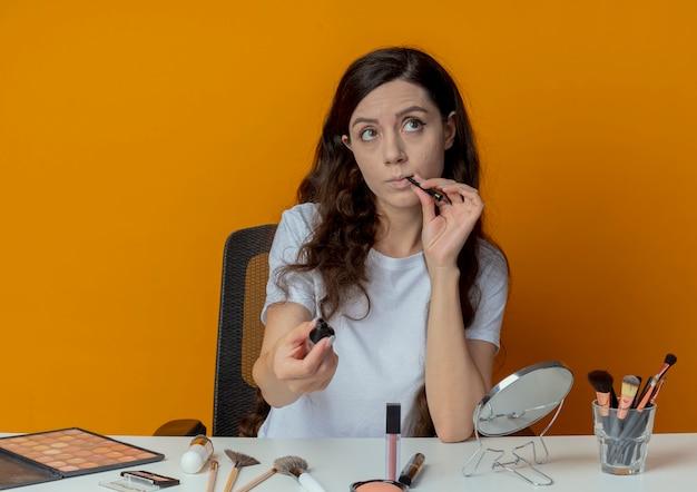 Przemyślana młoda ładna dziewczyna siedzi przy stole do makijażu z narzędziami do makijażu, wyciągając eyeliner w kierunku kamery, patrząc na bok i dotykając warg pędzlem do eyelinera