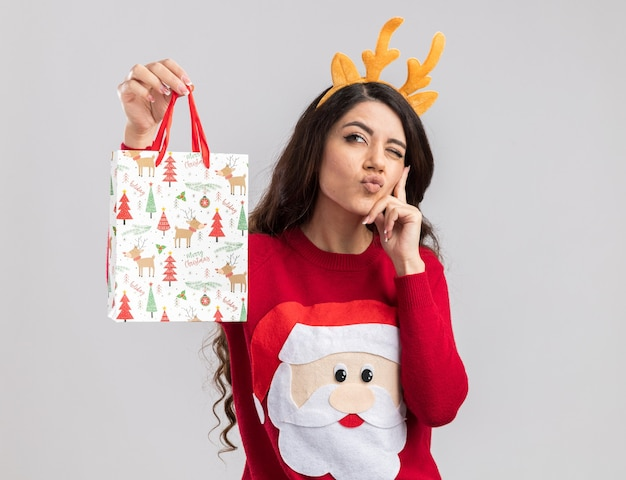 Przemyślana młoda ładna dziewczyna ubrana w opaskę z poroża renifera i sweter świętego mikołaja trzyma torbę z prezentami świątecznymi patrząc na bok, trzymając rękę na brodzie