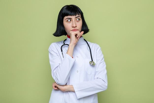 Przemyślana młoda ładna kaukaska dziewczyna w mundurze lekarza ze stetoskopem kładzie rękę na brodzie i patrzy na bok