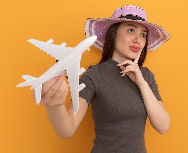 Przemyślana młoda ładna kobieta w kapeluszu rozciągająca model samolotu w kierunku przedniej, dotykająca twarzy palcem patrząca na bok odizolowana na pomarańczowej ścianie