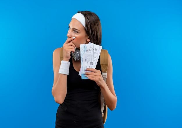 Przemyślana młoda ładna sportowa dziewczyna ma na sobie opaskę na głowę i opaskę oraz plecak i słuchawki na szyi, trzymając bilety lotnicze