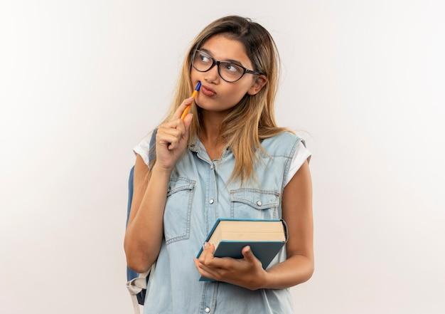 Przemyślana młoda ładna studencka dziewczyna w okularach iz powrotem trzymając książkę i dotykając twarzy piórem i patrząc na bok na białym tle na białej ścianie