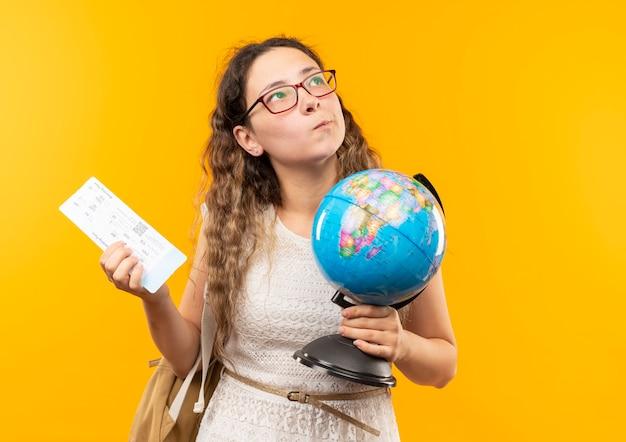 Przemyślana młoda ładna uczennica w okularach i plecaku trzyma bilet lotniczy i kula ziemska patrząc w górę na białym tle na żółtej ścianie