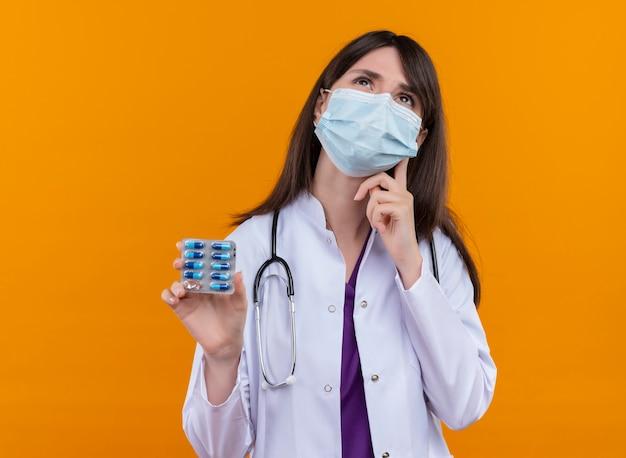 Przemyślana młoda lekarka w szlafroku medycznym ze stetoskopem nosi jednorazową medyczną maskę na twarz trzyma lekarstwo na izolowanym pomarańczowym tle z miejscem na kopię