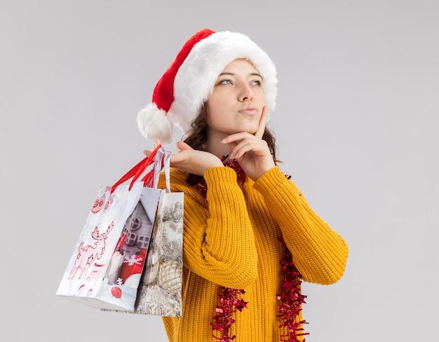Przemyślana młoda słowiańska dziewczyna z czapką mikołaja i girlandą na szyi kładzie rękę na brodzie i trzyma papierowe torby na prezenty patrząc z boku