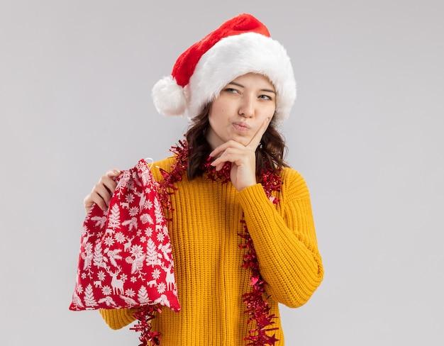 Przemyślana młoda słowiańska dziewczyna z santa hat i girlandą na szyi kładzie palec na podbródku i trzyma świąteczną torbę prezentową, patrząc na bok na białym tle na białej ścianie z miejscem na kopię