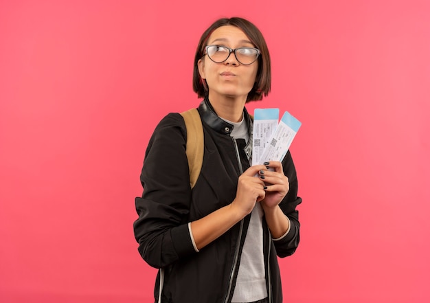 Przemyślana młoda studentka w okularach i plecak trzyma bilety lotnicze, patrząc na bok na białym tle na różowej ścianie