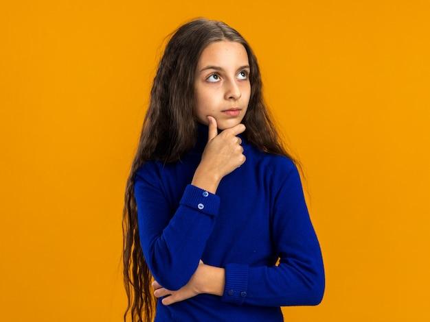 Przemyślana nastolatka patrząca w górę trzymająca rękę na brodzie odizolowaną na pomarańczowej ścianie z miejscem na kopię