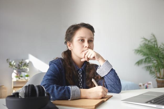 Przemyślana nastolatka w zwykłej koszuli siedzi przy biurku w domu z laptopem i słuchawkami, odrabia lekcje, pisze esej w zeszycie