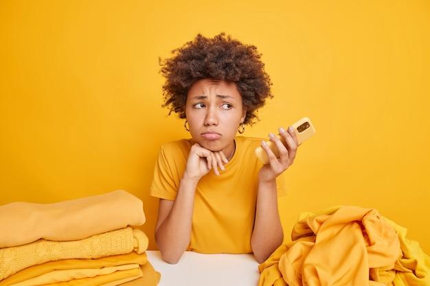 Przemyślana niezadowolona afroamerykanka trzyma smartfona w oczekiwaniu na telefon czuje się zmęczona po wykonaniu prac domowych składa pranie po praniu pozuje przy stole ze stosami wypranych ubrań wokół