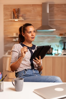 Przemyślana niezależna kobieta przy użyciu komputera typu tablet podczas pracy w godzinach nadliczbowych w domowej kuchni. korzystanie z nowoczesnych technologii o północy w godzinach nadliczbowych w pracy, firmie, pracy, karierze, sieci, stylu życia, bezprzewodowo.