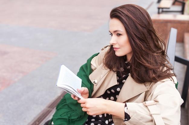 Przemyślana piękna dziewczyna czytanie książki w parku miejskim. piękna młoda kobieta na ulicy miasta. skopiuj miejsce