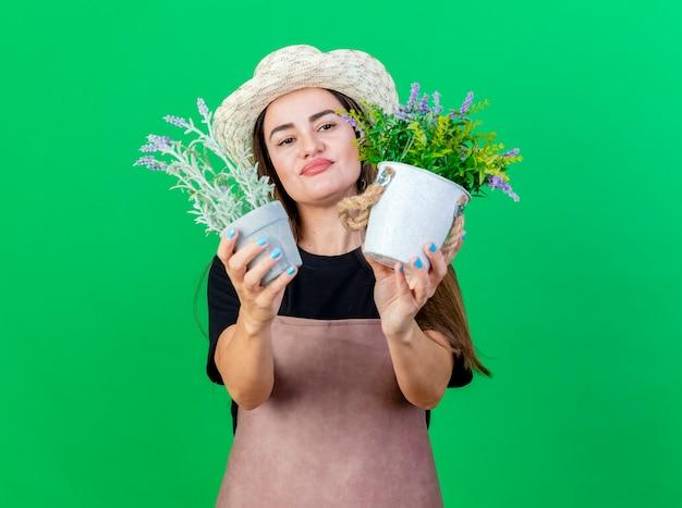 Przemyślana piękna dziewczyna ogrodnik w mundurze na sobie kapelusz ogrodniczy gospodarstwa i patrząc na kwiat w doniczce na białym tle na zielono