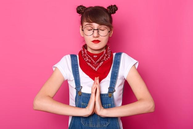 Przemyślana, poważna młoda dziewczyna układa ręce, zamyka oczy, stoi prosto i ma na sobie jeansowy kombinezon