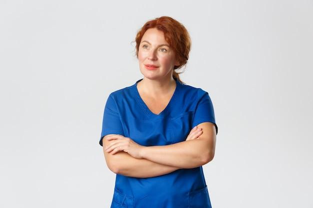 Przemyślana ruda pielęgniarka, lekarz lub lekarka w fartuchu z zaintrygowanym, zainteresowanym spojrzeniem w lewym górnym rogu, skrzyżowane ramiona na piersi, zwraca uwagę na baner, szare tło.