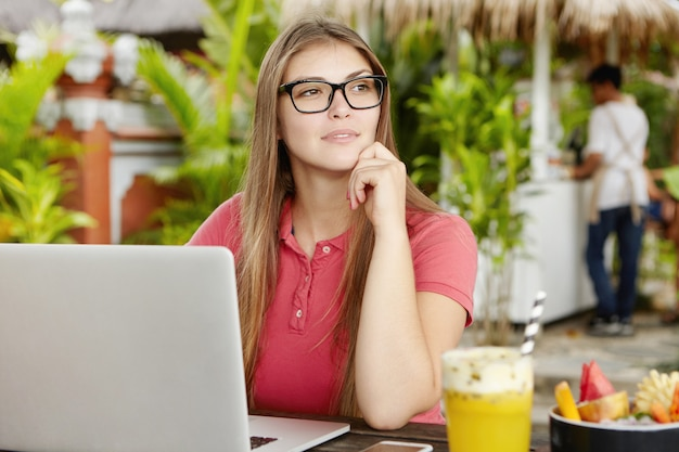 Przemyślana samozatrudniona kobieta w okularach siedząca przed otwartym laptopem, oparta na łokciu i odwracająca wzrok podczas pracy zdalnej podczas wakacji.