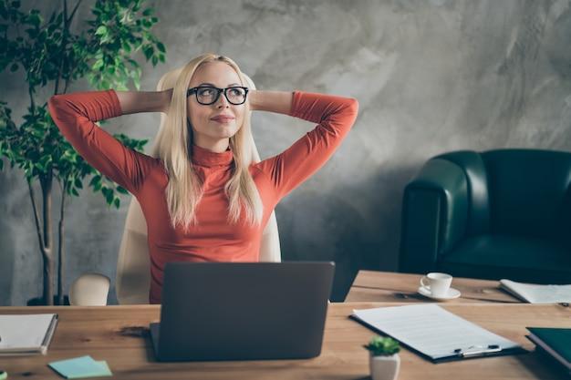 Przemyślana sekretarka piękna kobieta kończy pracę startową szefa projekt wygląd rozprostuj ręce pomyśl, kiedy w weekendy odpocznij, usiądź na stole, załóż czerwony golf na biurowym stanowisku roboczym
