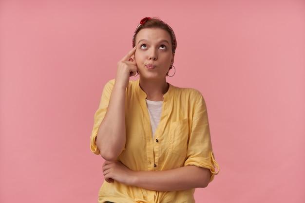 Przemyślana śliczna młoda kobieta w żółtej koszuli z opaską na głowie myśli i dotyka jej świątyni na różowej ścianie patrząc na pustą przestrzeń