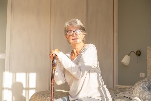 Przemyślana starsza kobieta opierając się na lasce siedząc na łóżku. samotna starsza kobieta siedzi w sypialni w domu. stara kobieta ciesząca się porannym słońcem w domu