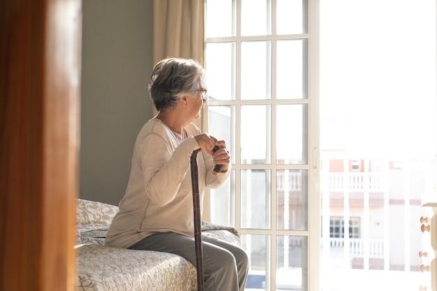 Przemyślana starsza kobieta opierając się na lasce siedząc na łóżku. samotna starsza kobieta siedzi w sypialni w domu. stara kobieta z siwymi włosami, oparta na lasce, siedząca na łóżku w domu